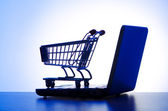 Silhoette of laptop and shopping cart — Stock Photo