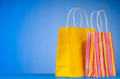 Colourful paper shopping bags against gradient background — Stock Photo