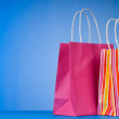 Colourful paper shopping bags against gradient background — Lizenzfreies Foto