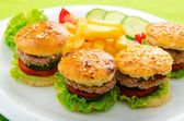 Plate with tasty mini burgers — Stock Photo
