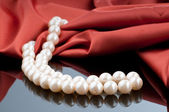 Pearls necklace on satin background — Photo