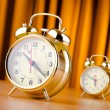Alarm clock against curtain — Stock Photo