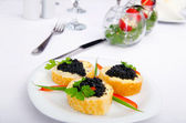 Black caviar served on bread — Stock Photo