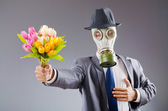 Businessman with gas mask and flowers — Stock Photo