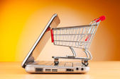 Shopping online with computer and cart — Stock Photo