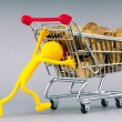 Smilies with shopping carts and coins - Stock Photo