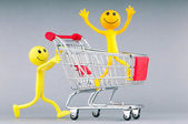 Shoppingvagn och glad smilies — Stockfoto