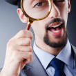 Detective and magnifying glass - Stock Photo