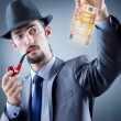 Detective looking at fake money - Stock Photo