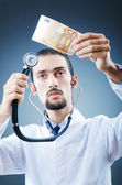 Doctor with money in studio — Stockfoto
