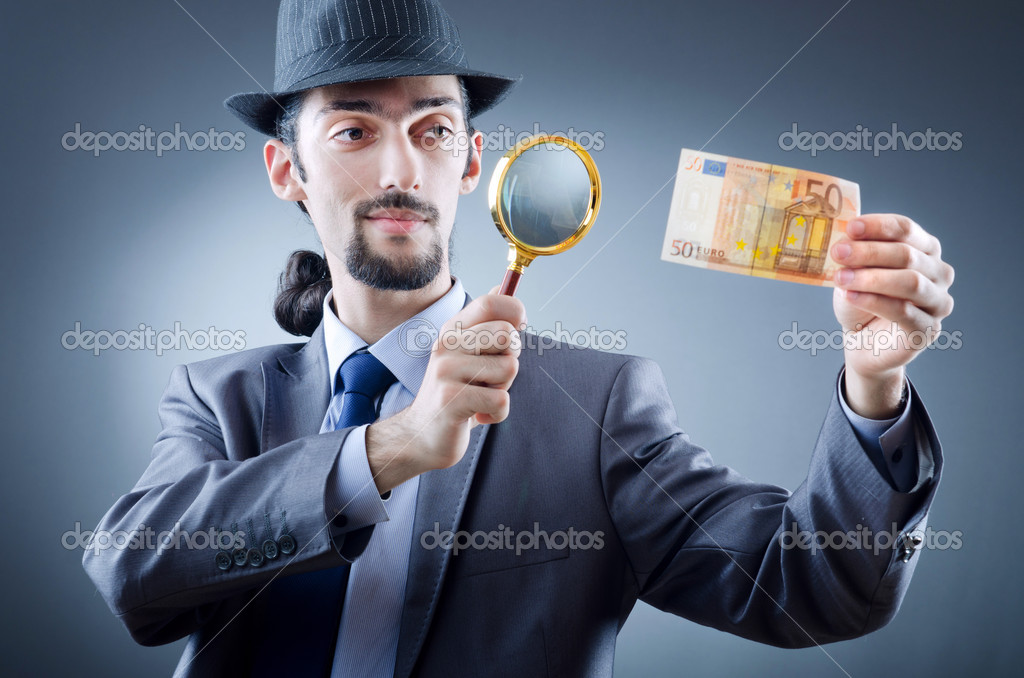 Detective looking at fake money  Stock Photo #7521343