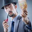 Detective looking at fake money — Stock Photo