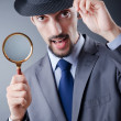 Stock Photo: Detective and magnifying glass