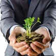 Businessman with gold seedlings and coins — Stock Photo