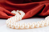 Pearls necklace on satin background — Stok fotoğraf
