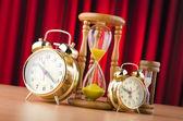 Reloj despertador y reloj de arena en el concepto de tiempo — Foto de Stock