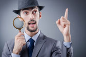 Detective and magnifying glass — Stockfoto