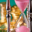 Hourglass and coins — Stock Photo