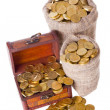Wooden chest and two bags filled with coins - Stock Photo