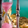 Hourglass and coins — Stockfoto #7095786