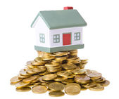 Toy small house standing on a heap of coins. — Stok fotoğraf