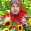 Little girl in a smart Sarafan is among sunflowers — Stock Photo