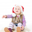 Little blonde girl in a fur jacket and a red Santa's cap sits on — Stock Photo #7869650