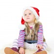 Little blonde girl in a fur jacket and a red Santa's cap sits on — Stock Photo #7869653