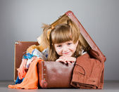 Girl joyfully sits in an old suitcase — Stock Photo