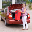 Young woman with a red suitcase in the car — Stock Photo