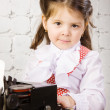 Little girl prints on the ancient typewriter — Stock Photo