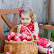 Little girl sits on a bench with a basket of apples — Stock Photo #7870524