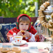 Girl in Russian national dress drinks tea from a samovar — Stock Photo #7870531
