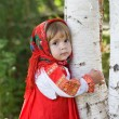 Stock Photo: Little girl in a smart Sarafan is embracing birch