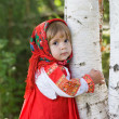 Little girl in a smart Sarafan is embracing birch — Stock Photo #7870540