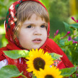 Stock Photo: Little girl in a smart Sarafan is among sunflowers