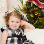 Little girl at a Christmas fir-tree. — Stock Photo