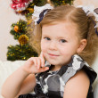 Foto Stock: Little girl at a Christmas fir-tree.