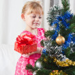 Girl with gifts near a New Year tree - Foto Stock