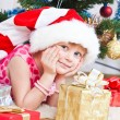 Girl with gifts near a New Year tree - Stock Photo
