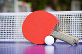 Two table tennis or ping pong rackets and balls on a blue table — Stok fotoğraf