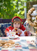 Girl in Russian national dress drinks tea from a samovar — Stock Photo
