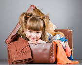 Girl joyfully sits in an old suitcase — Stok fotoğraf