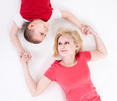 Mother and the son lie on a floor having joined hands. — Stock Photo