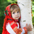 Little girl in a smart Sarafan is embracing birch — Stock Photo #7882381