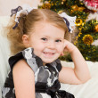 Stock Photo: Little girl at Christmas fir-tree.