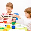 Boy and girl paint colors sitting at the table - Foto Stock
