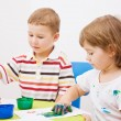 Boy and girl paint colors sitting at the table - Stock Photo