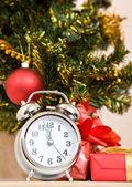 Pronto el año nuevo! horas y un regalo soporte bajo un árbol de abeto — Foto de Stock