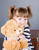Girl sits with a toy bear — Stock Photo